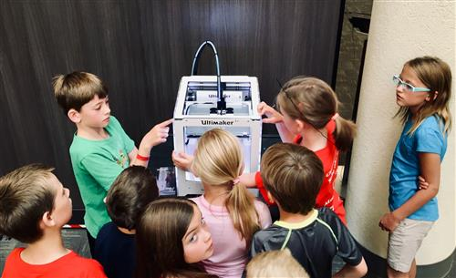 Students working with a 3D printer