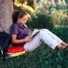 student reading book under tree