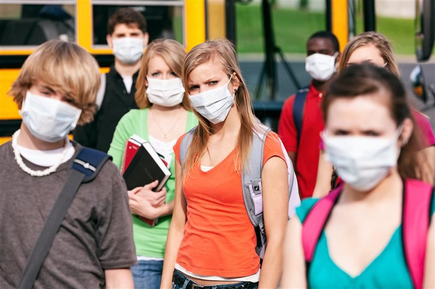 High school students standing next to bus wearing masks.