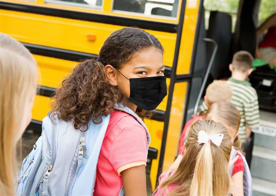 Elementary school students standing next to bus wearing masks.