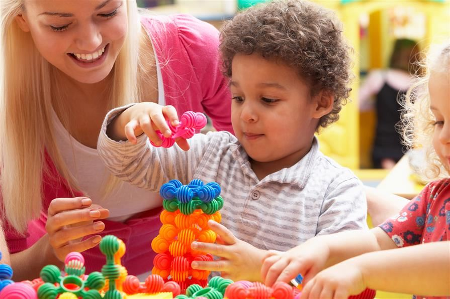 Young boy stacking ring blocks with teacher