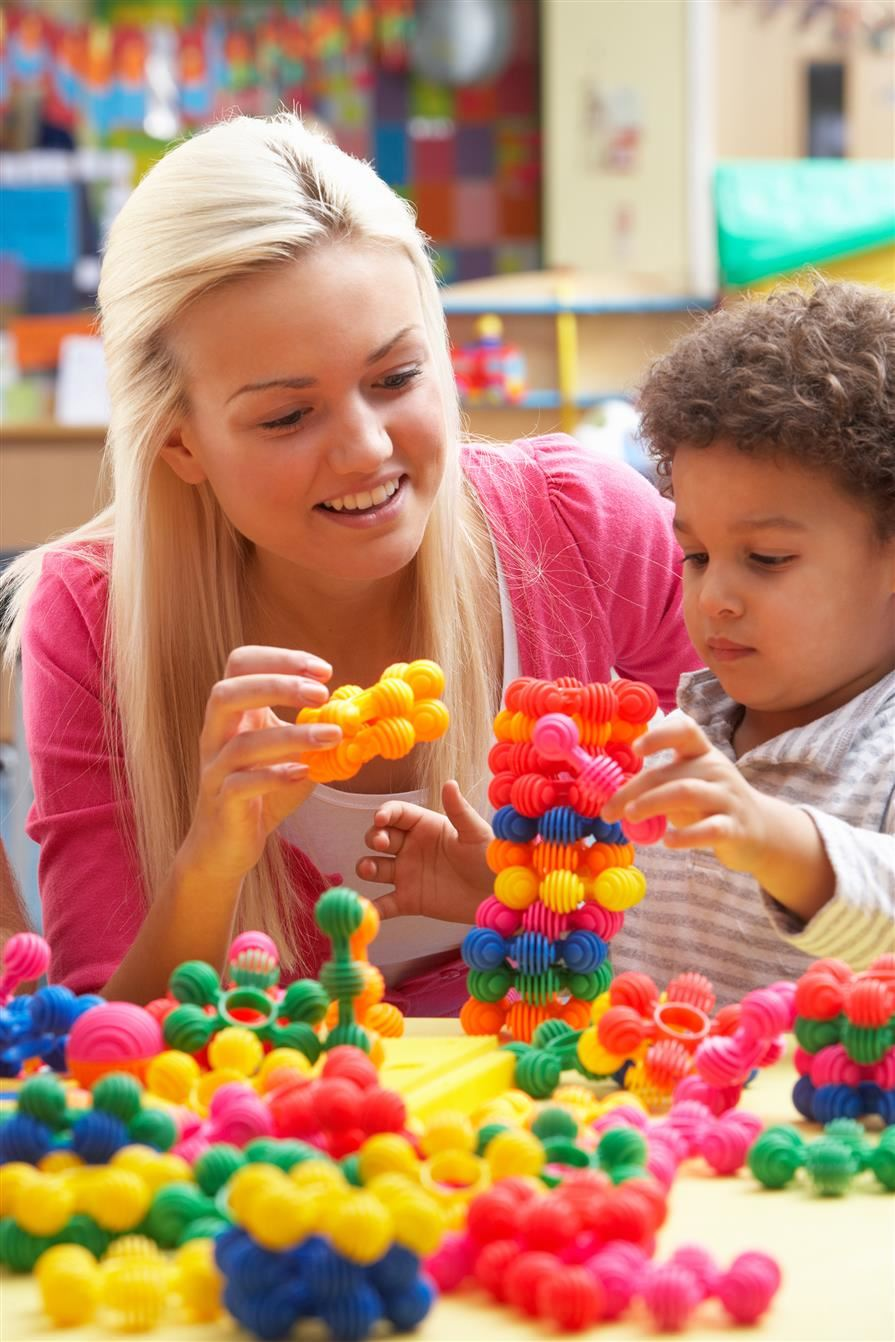 child playing with ring blocks with teacher